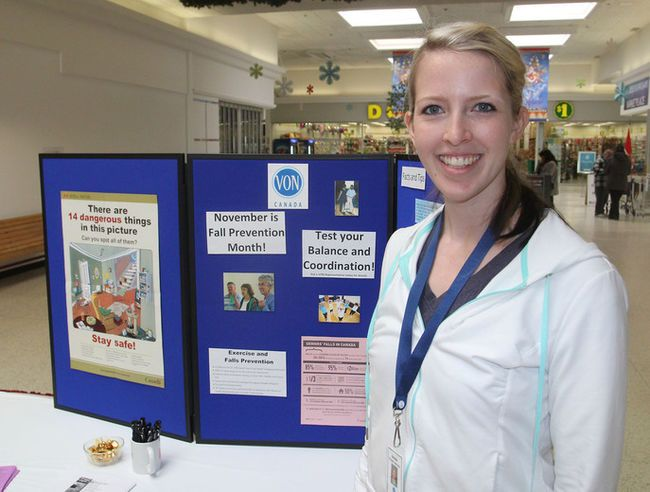 Danielle Anderson, a fitness instructor with the VON, stands in front of a recent display on falls prevention at the Frontenac Mall. (Michael Lea/The Whig-Standard)
