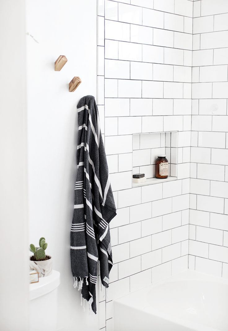 Black and white towel, gold hardware and white subway tile in bathroom