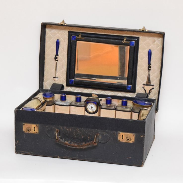 An antique leather vanity case. Included are all the original items: bottles, jars, valet brush, hair brush, German desk clock, detachable mirror, button hook, shoe horn, manicure kit and case. Most items are finished with a swirling cobalt blue and gold tone handle or top. A few items are stamped Schmidtt Germany...