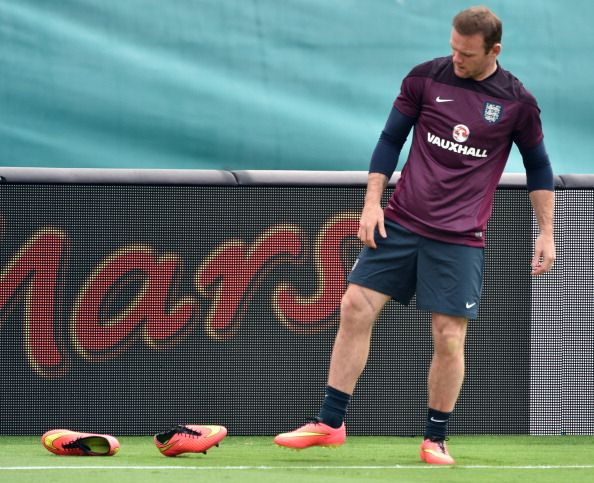 England forward Wayne Rooney changes his boots during his team's training session at Miami Sun Life Stadium in Miami Gardens, Florida on June 3, 2014.