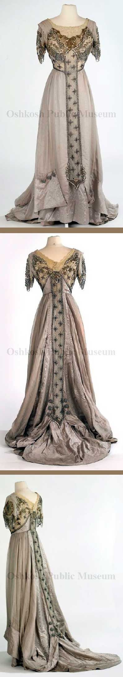 Gown, ca. 1905-1910. Gray moiré silk with overskirt of iridescent pink/gray chiffon that folds up at hem with 3 large buttons made of strands of silver beads. Neckline inset of off-white embroidered lace and gold lace. Bodice decorated on both sides with layers of gold, silver, and pearl beads and gold sequins. Oshkosh Public Museum. jαɢlαdy
