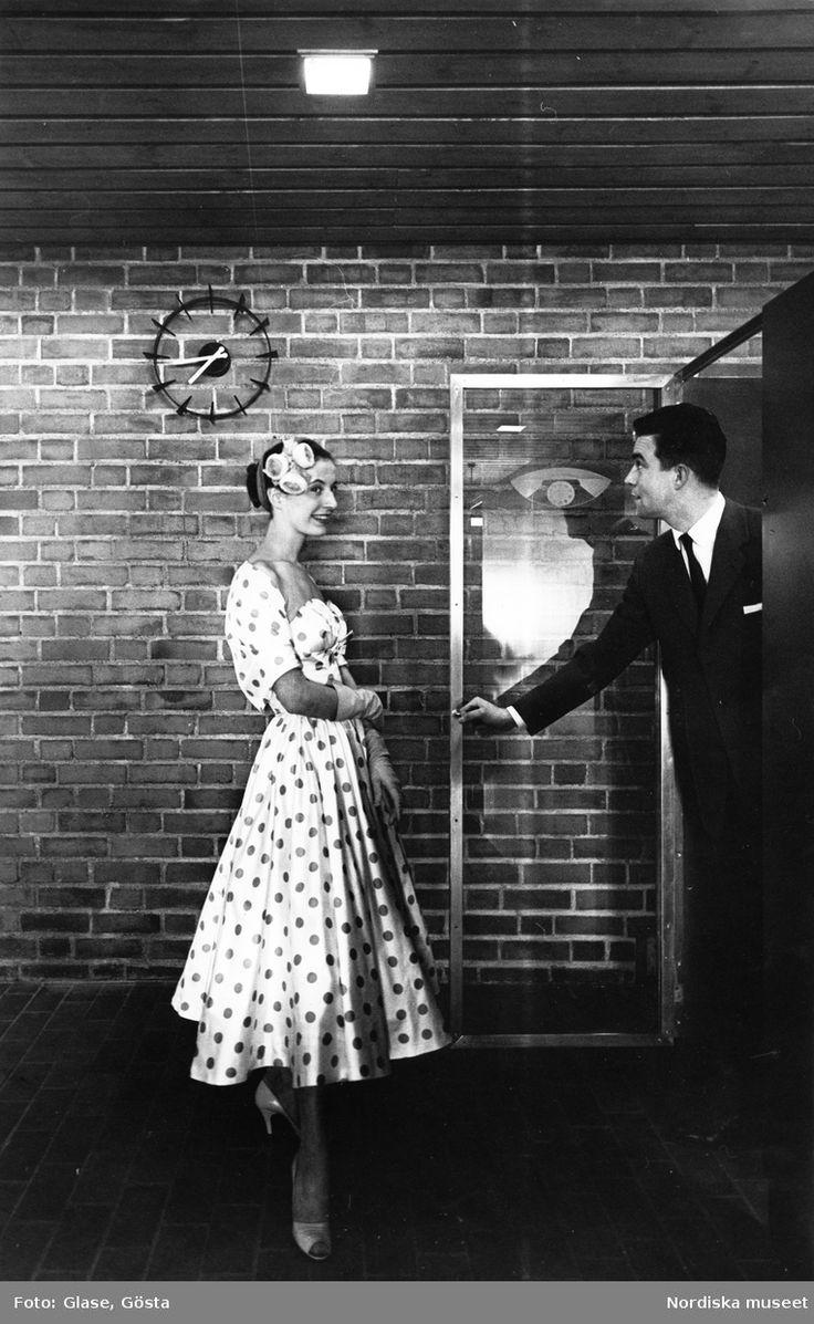 Kvinna i prickig klänning och bolero, handskar, högklackade skor och hårdekoration. Man i kostym öppnar dörr. Fotograf: Gösta Glase, ca 1950-1959
