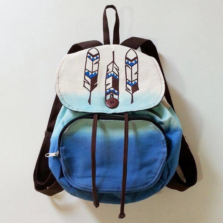 Mochila produzida com lona. <br>Técnica de tingimento em degradê em tons de azul. <br>Pintura artesanal com motivo pena tribal. <br>Fechamento com cordão e botão comum. <br>Possui um bolso interno e um externo com zíper.