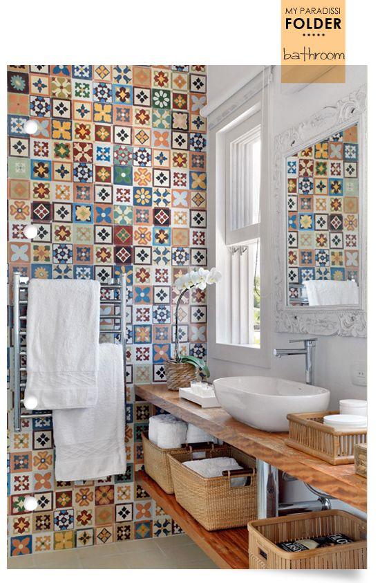 baño con pared de mosaico de azulejos, lavabo blanco sobre encimera de madera con balda. presupuestON.com