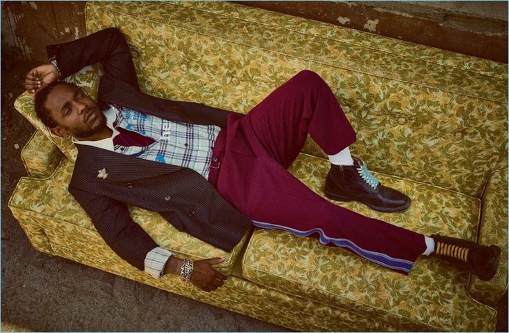 Relaxing, Kendrick Lamar wears a pinstripe jacket, side stripe trousers, and boots by Gucci. He also rocks a Lanvin shirt and Adidas Originals by Alexander Wang polo.