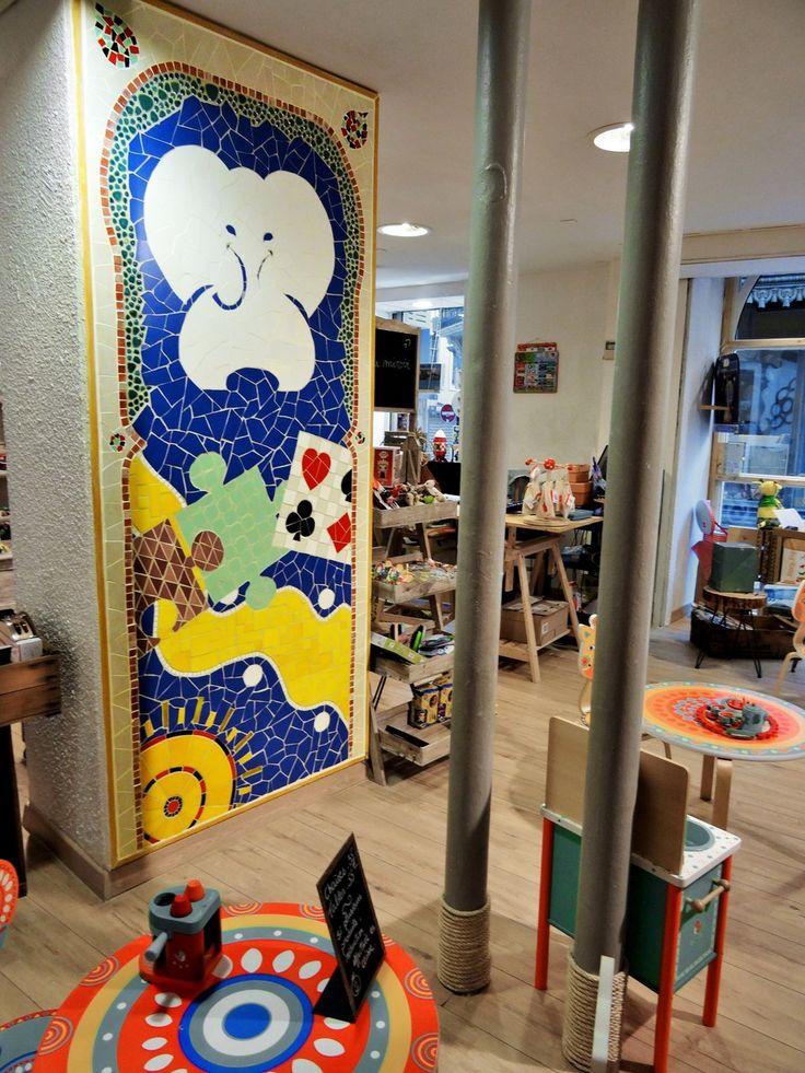 Fresque murale pour magasin et commerce. Ici, mosaïque avec le logo de l'enseigne intégré dans le décor pour un magasin de jouet au centre-ville de Narbonne. Création d'univers, d'ambiance pour commerce et magasin, vitrines ... Création en mosaïque pour décoration unique et personnalisée : contact@zam-creation.fr