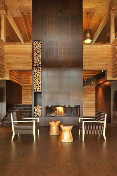 modern fireplace with great storage for logs & kindling that creates an artistic feature against the log wall backdrop