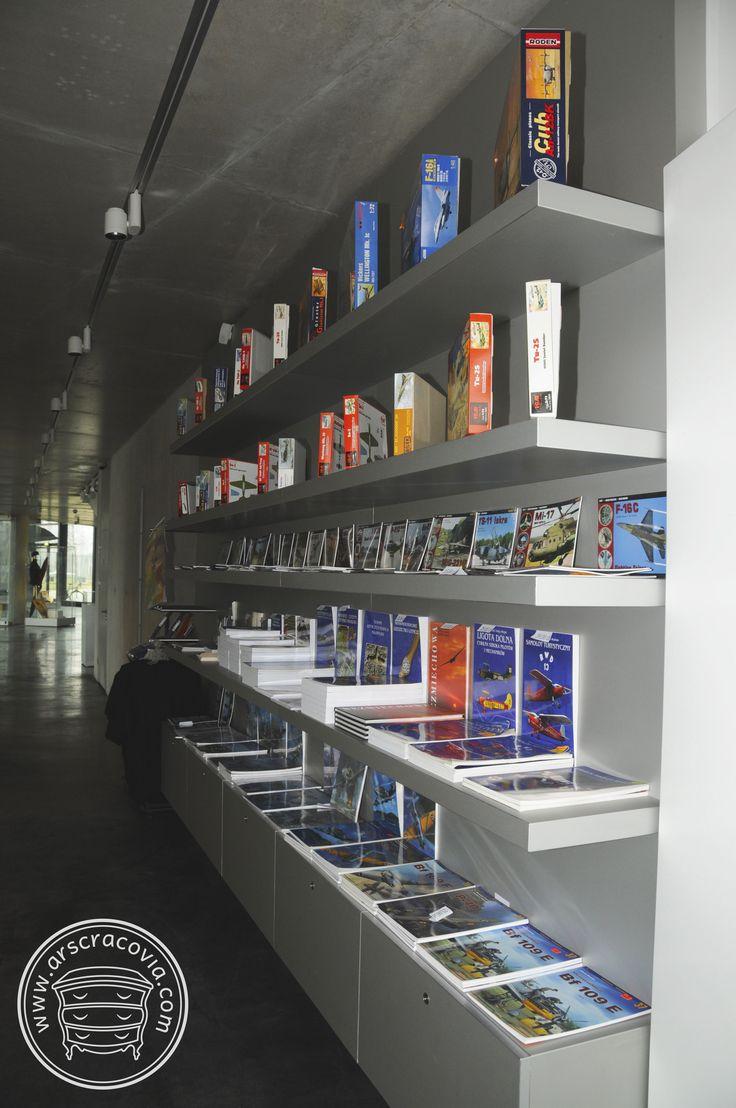 Zabudowa stała muzealnego sklepiku - szafki i regał z półkami wpuszczonymi w panelowe plecy, obłożone anodowaną blachą aluminiową grubości 1 mm.