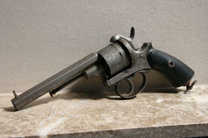Pinfire Revolver Lefaucheux Luik ca 1870  Franse revolver van het pinfire type Lefaucheux. Uniek zijn de uitgebreide graveringen op kamer trommel en loop. Ook op de kolf boven- en onderaan zijn graveringen. De trommel draagt het Luikse merkteken ELG. Opzij is het serienummer 26548 zichtbaar. De haan spant goed aan en kan hard afvuren. Hiervoor is echter vaak manuele hulp nodig. De haan kan ook soms loskomen van de trommel en kan manueel teruggezet worden. Een inwendige kuis- en smeerbeurt is…