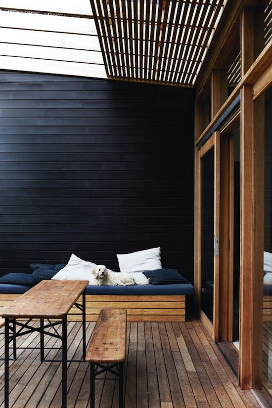 wooden deck, black wall.