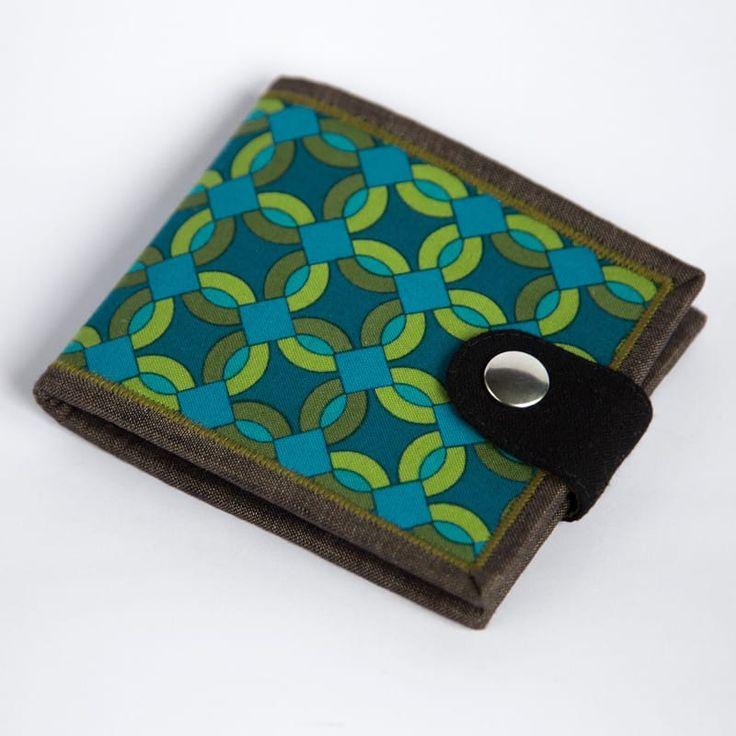Эксклюзивный брендовый мужской кошелек ручной работы от молодого отечественного бренда Yak Faino, сшитый вручную мастером из двух видов натуральной ткани –лен и хлопок. Лицевая внешняя сторона имеет принт сине-зеленого этнического кенийского узора, снабжена контрастной черной фронтальной кнопо