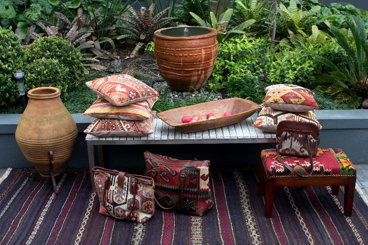 Cushions bags and stools sitting on beautiful old Afghan kilim.