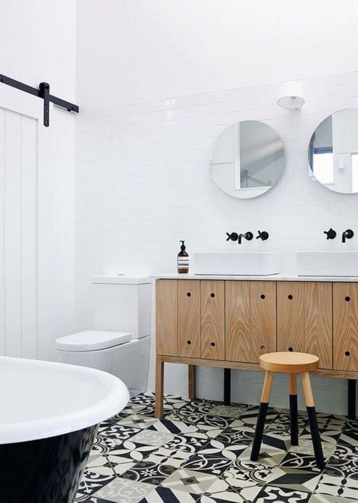 salle de bain scandinave, plancher en carreaux de ciment, baignoire à poser et robinets muraux noirs