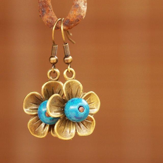 Modroočka Náušnice jsou vyrobeny z kovových kytiček barvy staroměděné a dřevěných korálků. Délka náušnic je 4 cm.