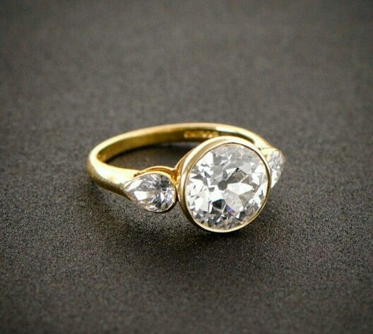 Yellow gold bezel three stone engagement ring. Round center with pear sides