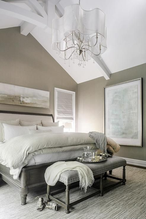 Taupe and gray bedroom features a wall painted taupe lined with a gray and taupe abstract panorama art placed above a  wood sleigh bed fitted with an upholstered sleigh headboard dressed in light taupe and gray bedding.