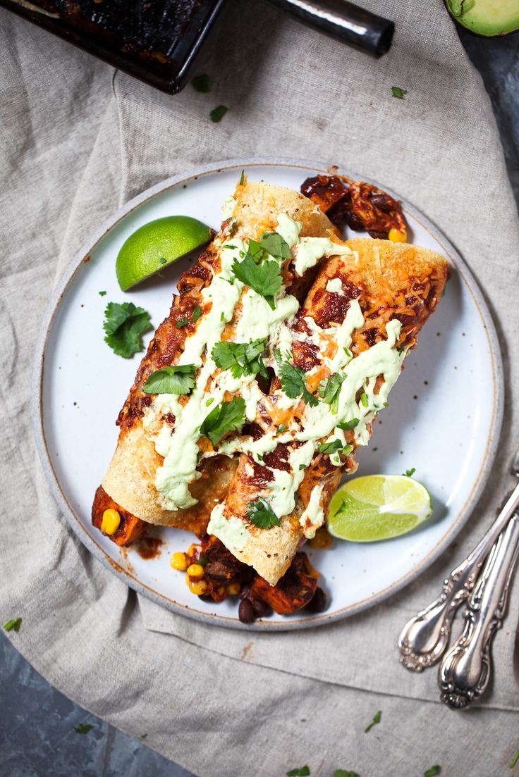 The best vegetarian enchiladas you'll ever eat: Sweet Potato Black Bean Enchiladas packed with flavor and topped with an amazing avocado lime sauce. Make them for dinner tonight!