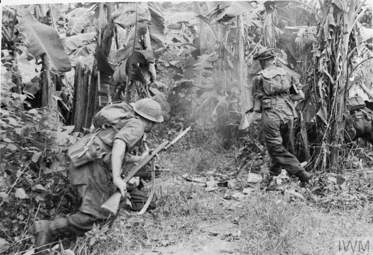 Troops attack a native 'basha' (bamboo hut) in a banana grove, 6 November 1944.