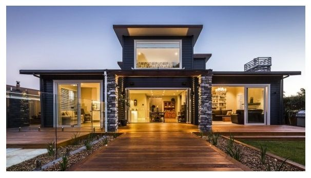 Schist stone pillars, dark-painted weatherboards and a strong symmetry enhance the visual drama of this new Waikanae house built by David Reid Homes. Photo Credit: Paddy Riley Photography.