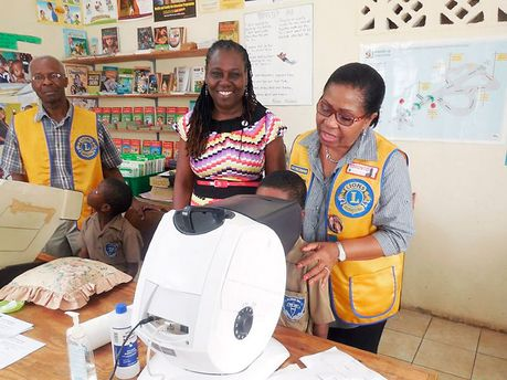 Members of the Lions Club of St Andrew, Keris Harper (right), first vice-president, and past President Burnett Price conduct vision screening on two students of the Allman Hill Primary and Junior High School in the Parkes Road community of West Rural St Andrew. Looking on is principal Georgia Henry. - Contributed