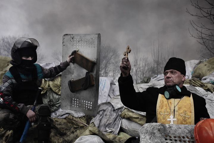 The 2nd prize in the Spot News Stories category of the 2015 World Press Photo Contest by Jerome Sessini, France, Magnum Photos for De Standaard shows an Orthodox priest blessing the protesters on a barricade in Kiev, Ukraine, Feb. 20, 2014. (AP Photo/Jerome Sessini, France, Magnum Photos for De Standaard)