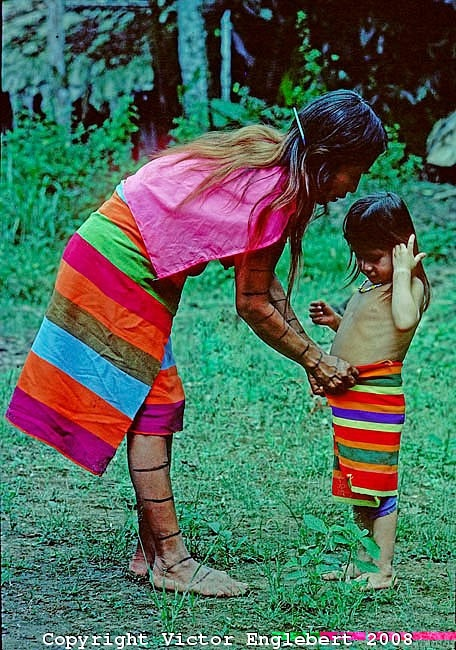 Ecuador. Near santo Domingo. Colorado Indian women adjusting her daughter's wrap-around.