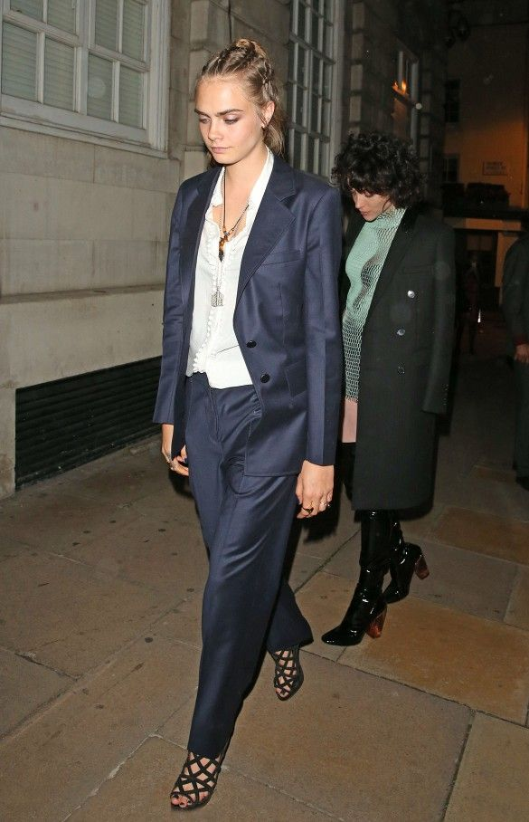 Cara Delevingne wears a white button-down shirt, layered necklaces, navy blue suit, and strappy heels
