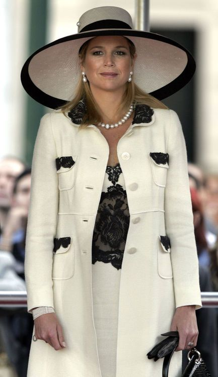 This white with black accents look good on her. Very elegant statement. Firm big hats looks good on her. She could add some fuchsia lipstick though.