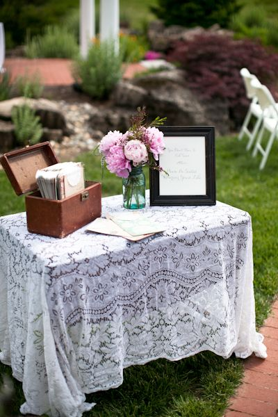 program table with vintage train case and lace linen
