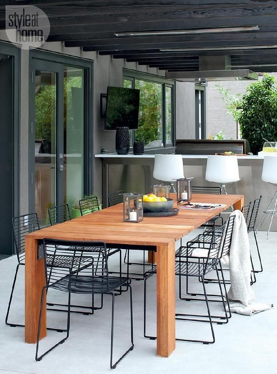 Contemporary covered patio is filled with a teak dining table surrounded by black metal dining chairs.