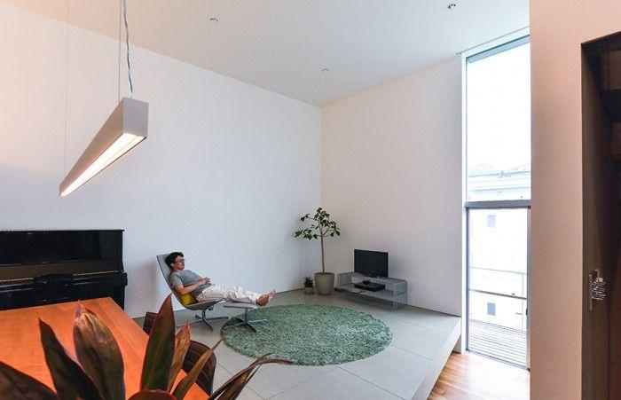 リビングの椅子でくつろぐ迎さん。ここから手前の壁面に映した大画面でホームシアターを楽しむ。