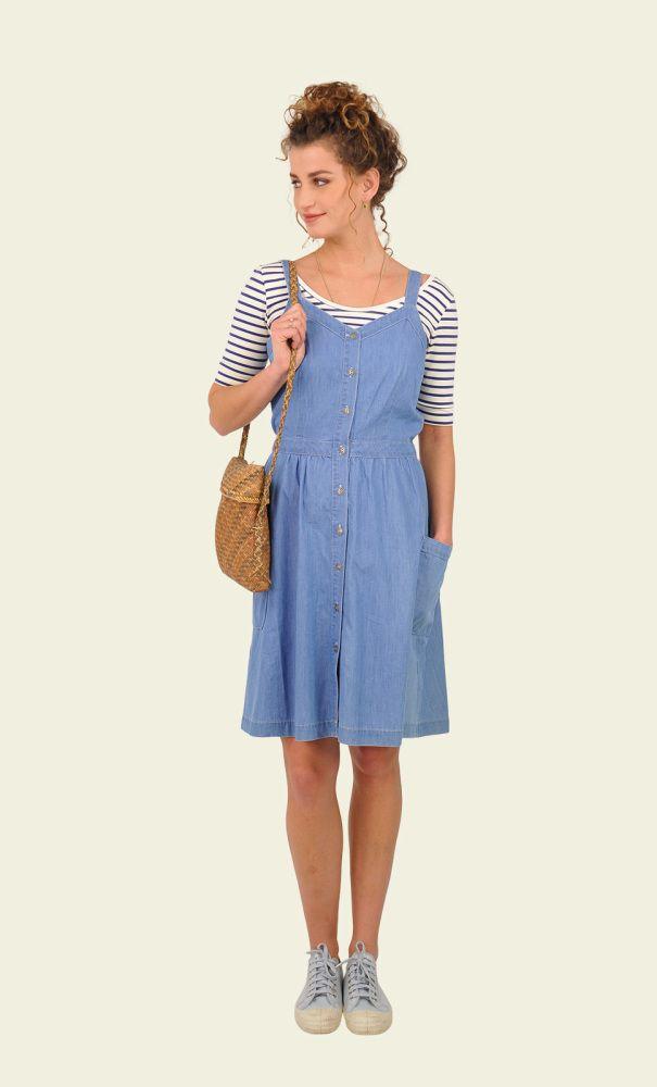 Een zomerse overgooier jurk van een lichte denim stof. De jurk heeft een V-hals, brede schouderbanden en een knoopsluiting over de gehele voorkant. De wijde rok is licht geplooid onder de vaste tailleband en heeft twee grote zakken aan de zijkant.