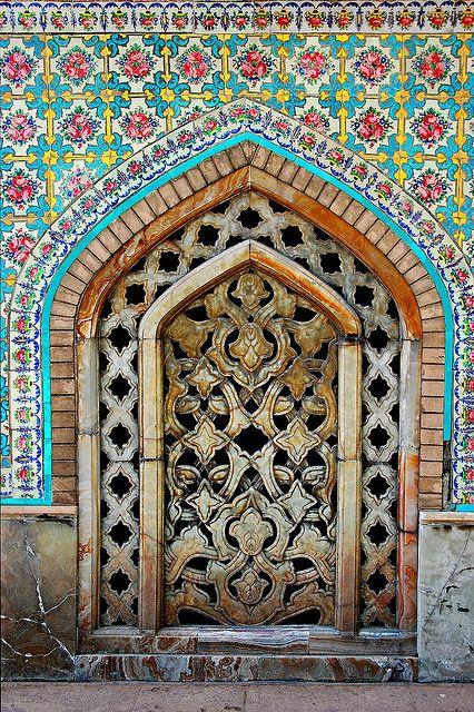 colorful tile work surrounds this wooden door
