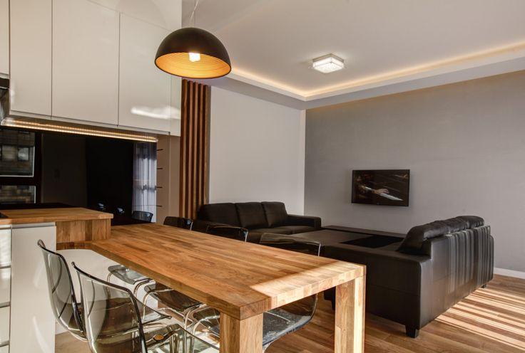 Salon w minimalistycznym stylu. Dwie czarne kanapy ustawione naprzeciw siebie, a pomiędzy stolik. Wnętrze ociepla drewniana podłoga.