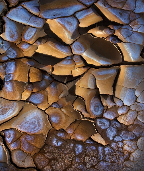 Colorful alkaline patterns mix with wet and dry desert mud cracks catching light on this great basin Playa./Marc Adamus