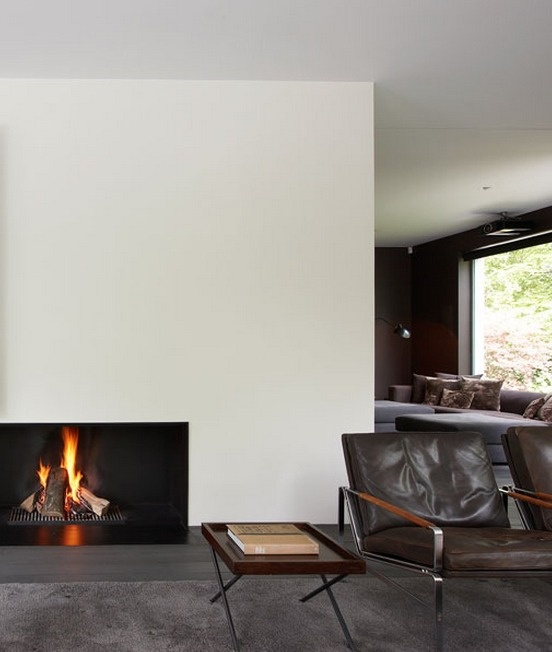 Warm, minimal interior. Clean fireplace +  midcentury furniture.