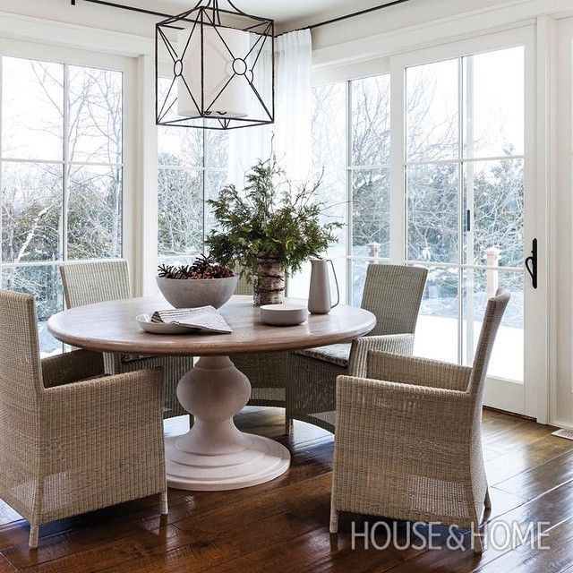 Wintery Dining Area In Sunroom With Round Pedestal Table, Dramatic Light  Fixture, Rattan Arm