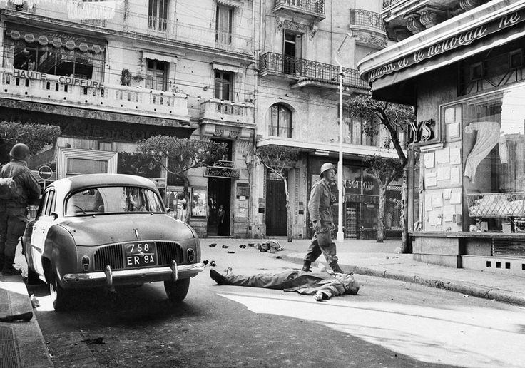 A French soldier walks past the body of settler killed on Rue D' Isley in Algiers, on March 26, 1962. Another European lies in the background amid debris of the battle that ensued when European settlers, carrying the French tricolor flag, marched on the center of town in response to a call by the terrorist secret army organization. The French armed forces forcibly dispersed the riot. Some sources estimate the result at 31 dead and 130 wounded. (AP Photo)