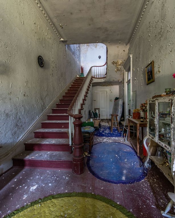A once-grand staircase springs from the ground floor up to the first floor of the abandoned home