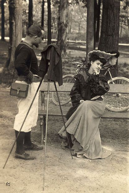 1890s: A young model, seated on a park bench, receives instructions from the photographer on which pose to assume