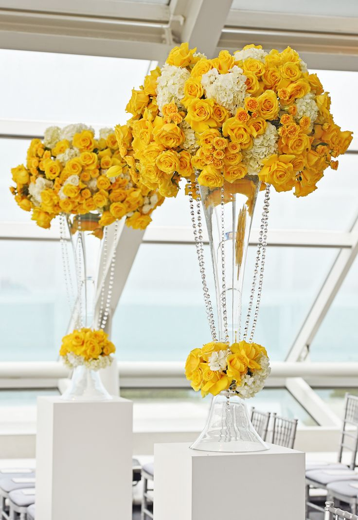 Vibrant yellow floral arrangements adorned the ceremony space. #WeddingCeremony  Photography: Carasco Photography. Read More: http://www.insideweddings.com/weddings/city-wedding-at-chicago-planetarium-with-purple-yellow-palette/688/