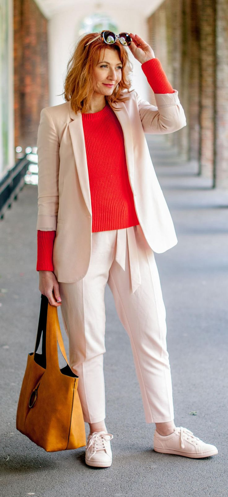 Bright spring/summer outfit: Blush pink trouser (pants) suit \ matching sneakers \ tomato orange red sweater \ yellow ochre suede hobo bag \ tortoiseshell sunglasses | Not Dressed As Lamb, over 40 style