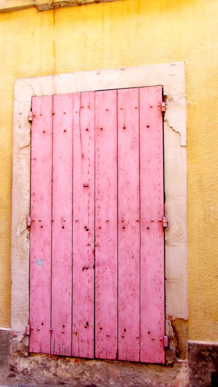 pink wooden door, yellow stucco wall, Arles, France