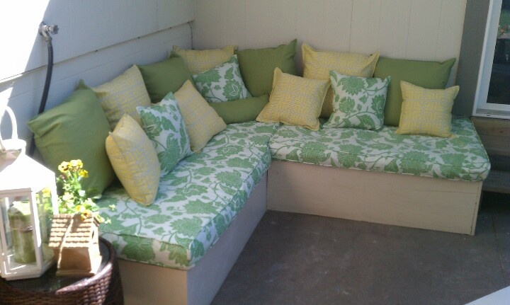 Pallet outdoor couch! Plywood coves the front, painted & sealed with poly. Cushions made out of a futon mattress, way cheaper than ordering foam for a custom piece! Covered with waterproof bed liner & outdoor fabric.