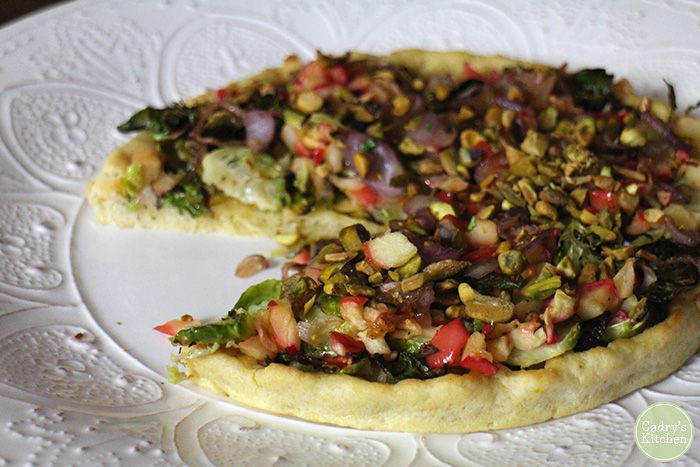 Roasted Brussels Sprouts pizza on a cornmeal crust with apples, caramelized onions & pistachios. It's a true taste of fall. Vegan.   cadryskitchen.com