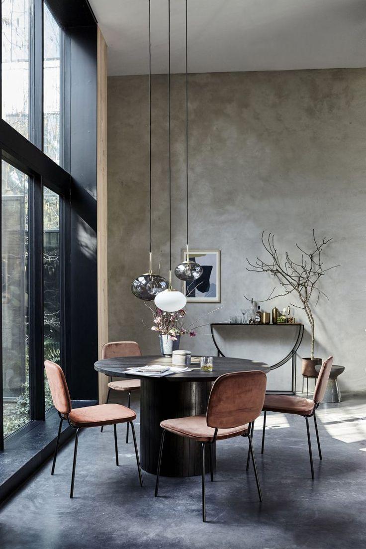 Zwarte ronde eettafel met velours stoelen in het zonnetje