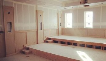 creating a custom home movie theater with stone walls and luxurious dark brown leather seating