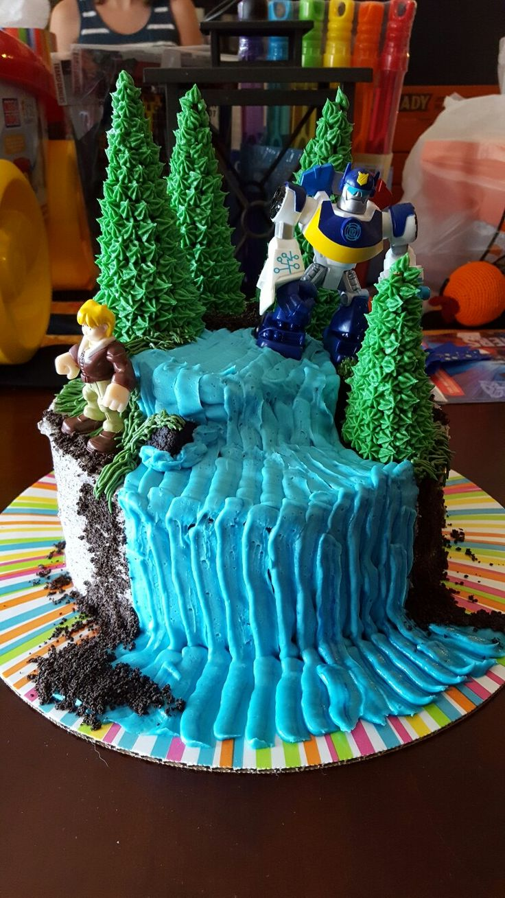 Rescue bots cake, exploring outside. Trees are sugar cones with piped butter cream. Oreo cake with Oreo frosting