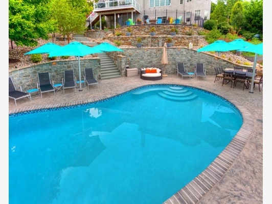 Beautiful backyard pool with a tiered wall off of the ...