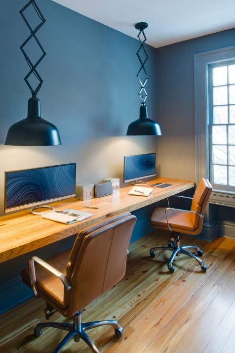This cool-toned contemporary home office spices up the workspace by adding fun pendant lights, a floating desk and comfy leather chairs.